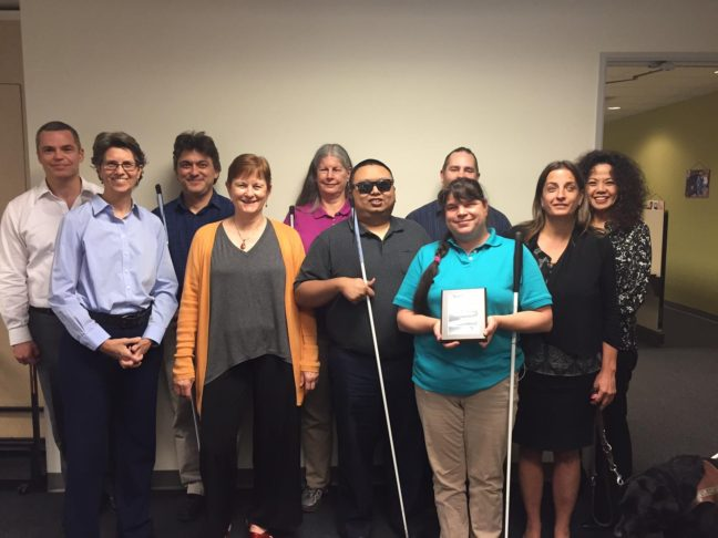Society for the Blind staff hold an award for Rehab Organization of the Year.