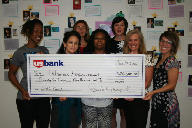 Women's Empowerment staff and graduates hold a check from U.S. Bank for $26,500.