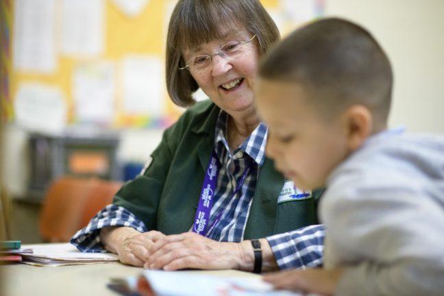 Boston, Massachusetts - May 07, 2015: AARP Experience Corps volunteer AnneMarie Desroches tutors second grader Josebelle Monge at Blackstone Innovation School in Boston, Massachusetts.    CREDIT: Matt Roth